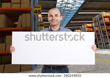 A man holding a blank board in a distribution warehouse, ideal for inserting your own message