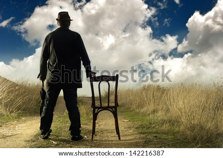 A man standing in the countryside watching at the cloudy horizon
