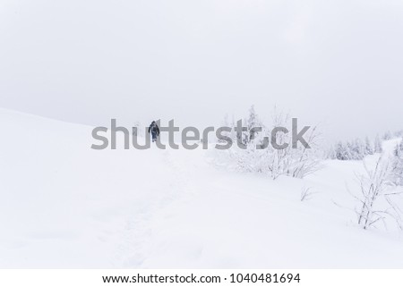 A man with a backpack in the mountains in the winter