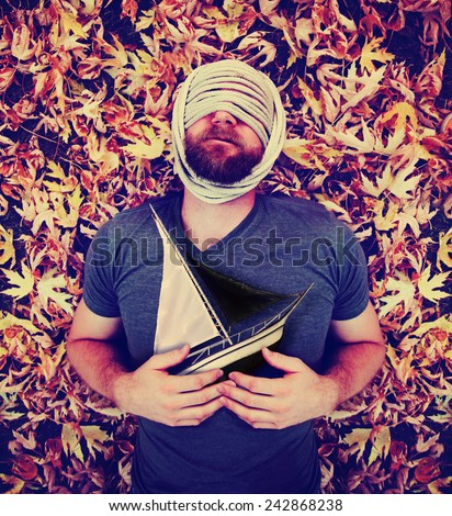 a man with a rope wrapped around his head laying in a pile of leaves holding a sailboat toned with a retro vintage instagram like filter effect  - stock photo