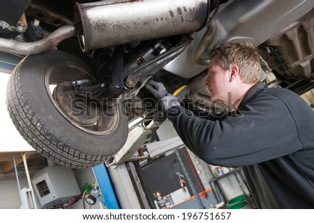 A mechanic is checking the technical state underneath a lifted car on a bridge in a garage.