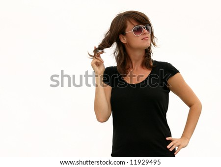 - a model posing against a light grey sky (almost white) and twisting her hair - stock photo
