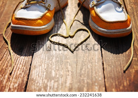 a pair of deck shoes on a nice wooden porch with the laces in a heart shape on a bright sunny day toned with a retro vintage instagram filter effect  - stock photo