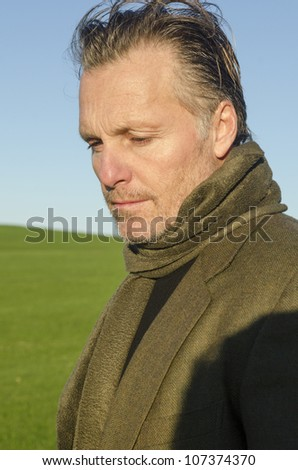 A pensive looking mature man with beard wearing scarf - stock photo