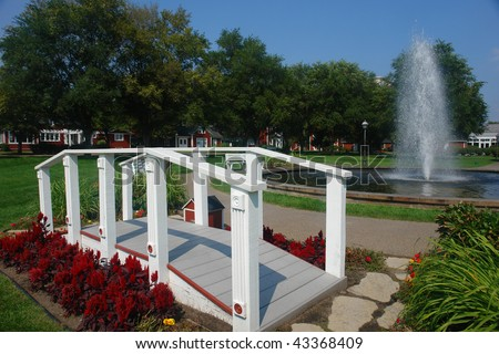 A picture of small foot bridge and sprinkler in summer garden  park