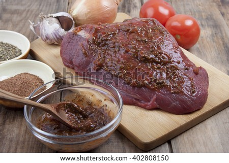 A piece of raw meat beef on a cutting board, spices, herbs and sauce.