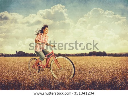 a pretty girl riding her bike in a field full of yellow flowers toned with a retro vintage instagram filter app or action effect  - stock photo
