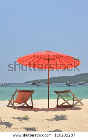 A red beach umbrella and chaise lounges on white sand. Tropical paradise on the bank of the azure sea