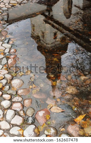 a reflection of the Duomo in a puddle on a cobblestone pavement, Tallinn - stock photo