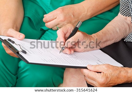 A senior woman's hand signing a document - stock photo