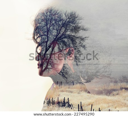 a serious looking woman side profile toned with vintage tones for a retro look and a double exposure with a field and trees - stock photo