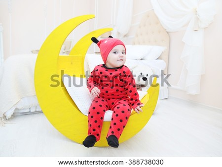 A small child dressed in a red suit with black polka dots. Children's interior. White light room with a cot, the moon toy, a Teddy bear. - stock photo