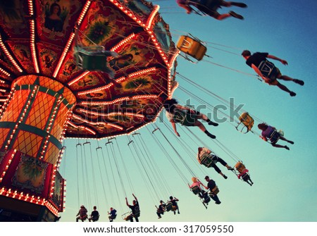 a swinging fair ride at dusk toned with a retro vintage instagram filter app or action with motion blur and grainy effect added for a grunge look and feel  - stock photo