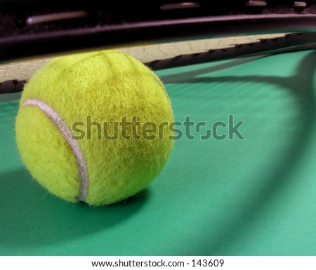 A tennis ball under a racket and some interesting shadows