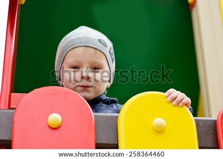 a toddler funny boy on the playground - stock photo