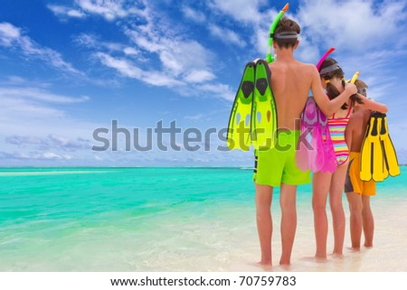 A trio of kids on the beach with fins and snorkels. - stock photo