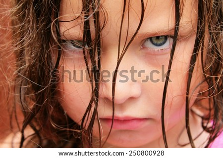 A very grumpy young girl with green eyes - stock photo