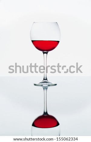 A wine glass with liquid poured is on a white background
