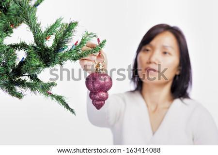 A woman hangs a Christmas ornament on a tree. - stock photo