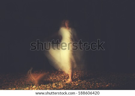 a woman in a very foggy forest at night - stock photo