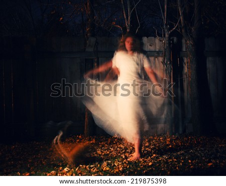 a woman in a very foggy forest at night with a yellow cat and motion blur caused by slow shutter speed - stock photo