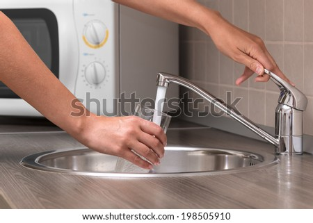 A woman, pouring water from faucet into a glass at a kitchen. - stock photo