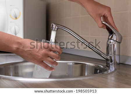 A woman, pouring water from faucet into a glass at a kitchen.