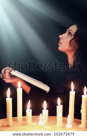 A woman prays with a book