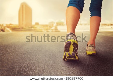 a woman with an athletic pair of legs going for a jog during sunrise or sunset - healthy lifestyle concept done with an instagram like filter  - healthy lifestyle concept  on a cityscape background - stock photo