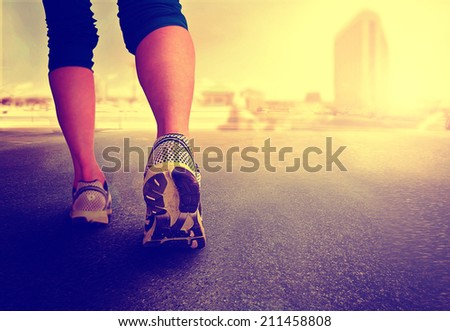 a woman with an athletic pair of legs going for a jog or run during sunrise or sunset - healthy lifestyle concept toned with a retro vintage instagram like filter  - stock photo