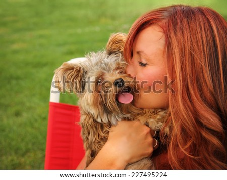 a woman with her beautiful dog cuddling outside at a park  - stock photo