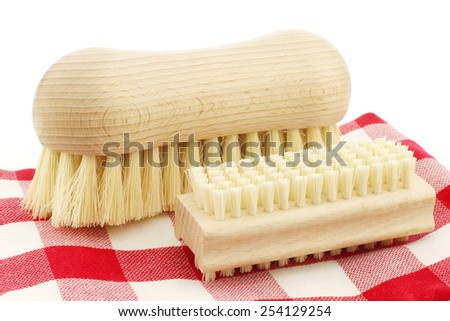 a wooden nail brush and a wooden household brush on a red and white checkered kitchen towel on a white background - stock photo
