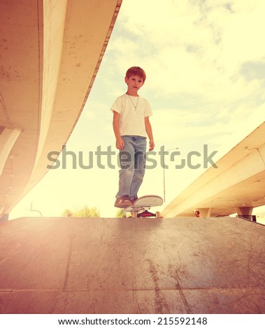 a young boy skateboarding in an urban setting done with a retro vintage instagram filter