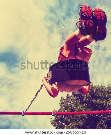 a young boy swinging in a playground toned with a vintage retro instagram filter app or action effect - stock photo