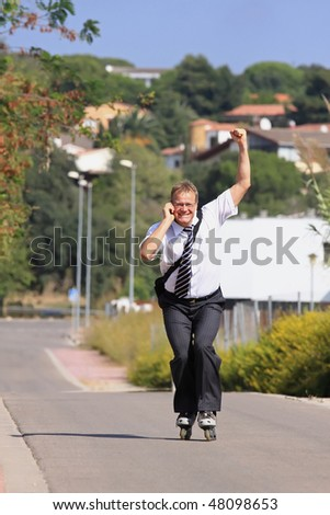 A young businessman with a roller skate received very good news - stock photo