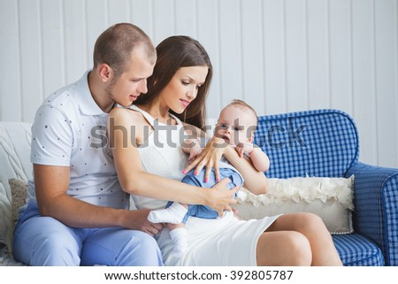 a young family with a nice and sweet little baby sitting on the sofa in a bright interior.