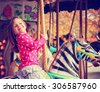 a young girl riding on a merry go round at the zoo toned with a retro vintage instagram filter effect app or action - stock photo