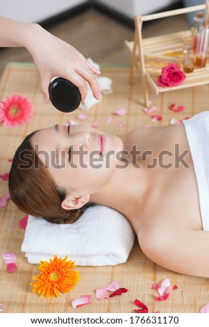 A young lady enjoying stone massage at spa