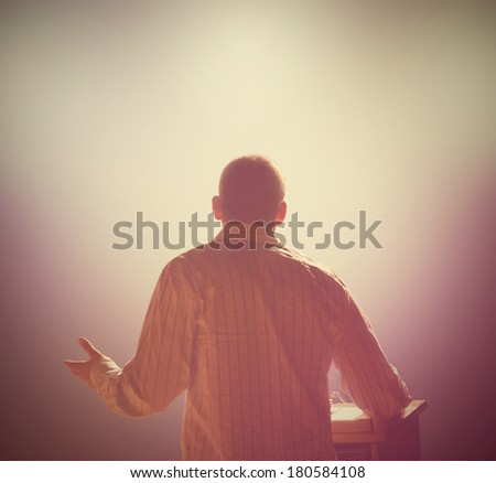a young man in front of a podium and an audience  - stock photo