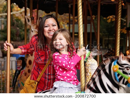 a young mother and her daughter riding on a merry go round at t - stock photo