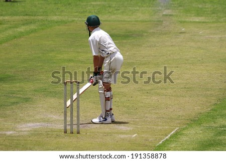 A young school boy cricket player is preparing to attack the ball. - stock photo