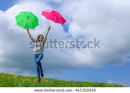 a young woman in a meadow of dandelion with two pink and green umbrella