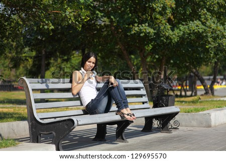 A young woman sitting on a bench, near the university, listenin