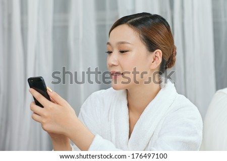 A young woman talking by cell phone in spa salon