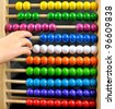 Abacus with many colorful beads and child's hand - stock photo