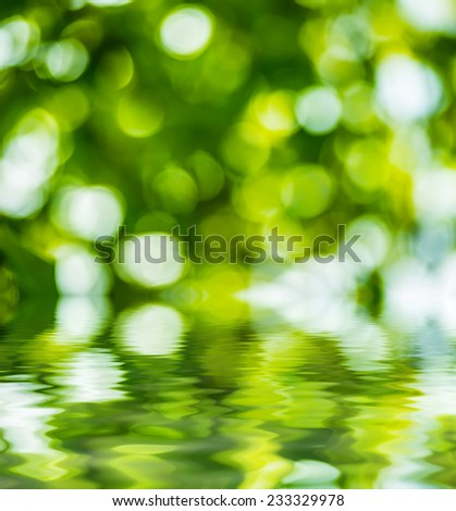 Abstract circular green bokeh reflected in water.  - stock photo