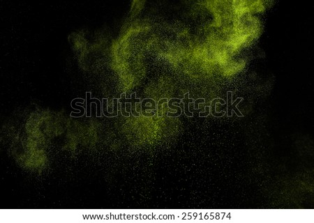 Abstract green powder explosion  on black background.