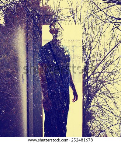 Abstract soft focused duotoned double exposure portrait of man in a doorway and black forest toned with a retro vintage instagram filter  - stock photo