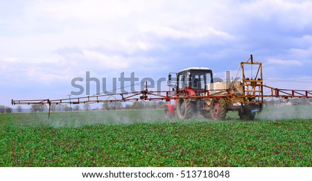 Adding  chemical weed and pest killers on a spring field with the plantlet of rape