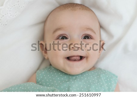 Adorable little baby girl laughing, creeping & playing in the studio, on white background